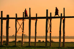 Silhouetted people on U Bein Bridge at sunset, Amarapura, Myanma Stock Photos