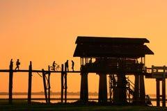 Silhouetted people on U Bein Bridge at sunset, Amarapura, Myanma Stock Image