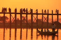 Silhouetted people on U Bein Bridge at sunset, Amarapura, Myanma. Silhouetted people on U Bein Bridge at sunset, Amarapura, Mandalay region, Myanmar Royalty Free Stock Images