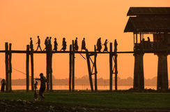Silhouetted people on U Bein Bridge at sunset, Amarapura, Myanma Stock Images