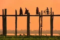 Silhouetted people on U Bein Bridge at sunset, Amarapura, Myanma Stock Photo
