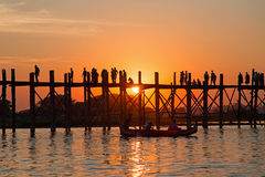 Silhouetted people on U Bein Bridge at sunset in Myanmar Stock Image