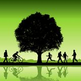 Silhouetted people under tree Stock Photo