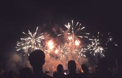 Silhouetted People Watching a Fireworks Display. Crowd of Silhouetted People Watching a Fireworks Display for New Years or Fourth of July Celebration, Horizontal Royalty Free Stock Images