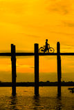 Silhouetted person with a bike on U Bein Bridge at sunset, Amara Stock Image