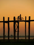 Silhouetted person on with a bike on U Bein Bridge at sunset, Am Royalty Free Stock Photo
