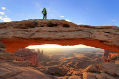 Silhouetted person standing on top of Mesa Arch, Canyonlands Nat stock photo