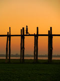 Silhouetted person on U Bein Bridge at sunset, Amarapura, Myanma Stock Image