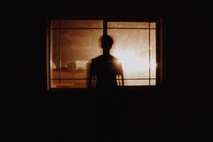 Silhouetted person by window in home
