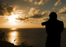 Silhouetted Photographer Shooting. Photographer Silhouette Shooting Sea at Sunset Royalty Free Stock Images