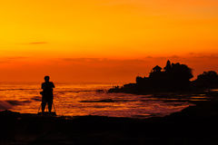 Silhouetted of photographer and Tanah Lot at sunset, Bali, Indon Stock Photography