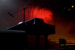 Silhouetted Piano Shape on Stage. Silhouette shape of a piano in the foreground. Steps leading up to the elevated stage are lined with bright beaded lights stock photo