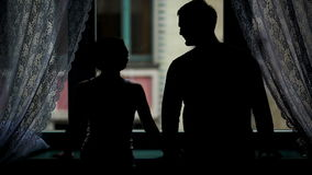 Silhouetted Portrait of the Couple near the Window. Woman is Taking Man Hand in Her, They are Kissing and Hugging with stock video footage