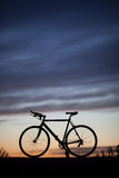 Silhouetted race bike in sunset Stock Images