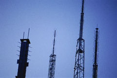Silhouetted radio antennas Royalty Free Stock Images