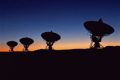 Silhouetted radio telescope dishes Stock Photos