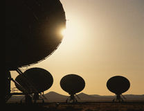 Silhouetted radio telescope dishes Royalty Free Stock Photography