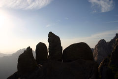 Silhouetted rocks on mountain. With blue sky and cloudscape background Stock Images