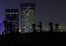 Cameras on a rooftop at night. Silhouetted row of cameras on tripods lined up overlooking an illuminated city with skyscrapers on a rooftop at night Royalty Free Stock Images