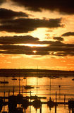 Silhouetted sailboats in harbor at sunset Royalty Free Stock Images