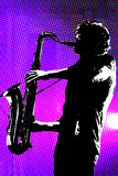 Silhouetted saxofonspelare royaltyfria bilder