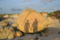 Silhouetted Shadows Holding Hands on Aruba`s North Shore stock image