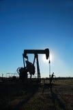 Silhouetted stålar för oljepump arkivfoto