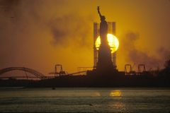 Silhouetted Statue of Liberty with scaffolding at sunset, New York City, New York Stock Photos