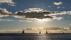 Silhouetted sväva sätter på land segelbåtar på solnedgången på Waikiki, Honolulu, den Oahu ön, Hawaii, USA royaltyfri bild