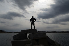 Silhouetted Teen in Cedar Point Scituate. Teen silhouetted on rocks in Scituate on a rock jetty Royalty Free Stock Photos