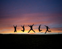 Silhouetted teens jumping in sunset royalty free stock photo