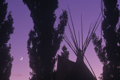 Silhouetted Teepee and trees against purple sky & crescent moon Royalty Free Stock Image