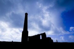 Silhouetted Tin Mine Buildings. Dramatic silhouette of derelict chimney stacks and buildings at a Cornish tin mine. Personal post-production treatment with Stock Photography