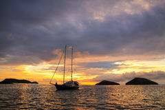 Silhouetted tourist sailboat at sunrise anchored near Chinese Ha. T island in Galapagos National Park, Ecuador Stock Image