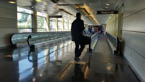 Silhouetted traveler at an airport automated walkway Royalty Free Stock Photography