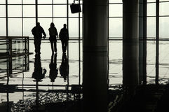 Silhouetted travellers in an airport terminal Stock Photo