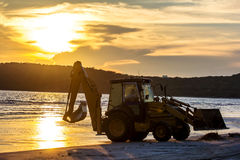 Silhouetted wheel loader Excavator unloading sand Stock Photo