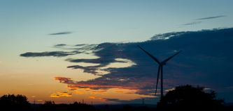 Silhouetted Wind Turbine at Sunset. A silhouetted wind turbine against a dark sky at sunset royalty free stock photography