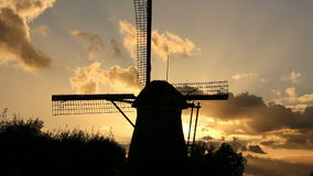 A Silhouetted Windmill and a Flock of Birds on its Wicks stock footage