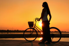 Silhouetted woman with bicycle at Mekong river Royalty Free Stock Photos