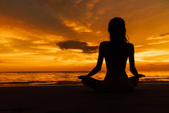 Silhouetted woman in lotus pose on background beautiful sunset on sea. Silhouette woman yoga in lotus pose on background beautiful sunset on sea. Close up girl stock photo