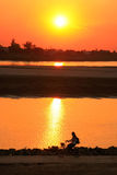 Silhouetted woman riding at Mekong river Royalty Free Stock Photo