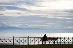 Silhouetted woman sitting on bench at lake constance Stock Photos