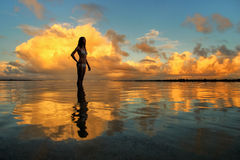 Silhouetted woman standing in a water at sunset on Taveuni Islan Royalty Free Stock Image