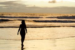 A silhouetted woman walking near the sea on a beach with the sun rising and the sunrays reflecting in the sea water. Stock Photo