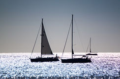 Silhouetted Yachts. Three yachts silhouetted against a silvery sea stock photos