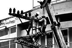 Silhouetteelektrikerarbetet på elektricitet postar Arkivfoto