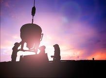 Silhouetteer een mensenbouwvakker in een bouwterrein over Bl Stock Foto