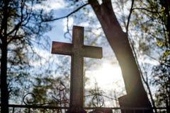 Silhouetteer het kruis op zonsondergang bij begraafplaats royalty-vrije stock fotografie