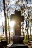 Silhouetteer het kruis op zonsondergang bij begraafplaats stock foto's
